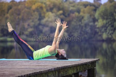 frau uebt yoga auf steg an