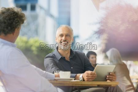 smiling geschaeftsleute sprechen kaffee zu trinken