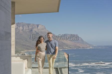 smiling couple walking on luxury balcony