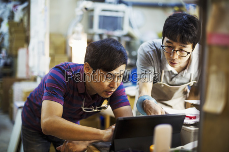 two men using a laptop computer
