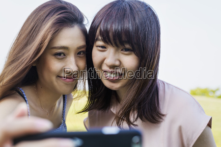 two smiling young women with long