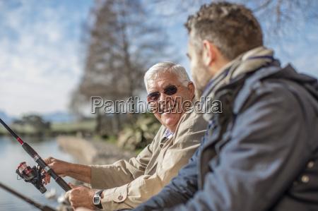 senior man and adult son fishing