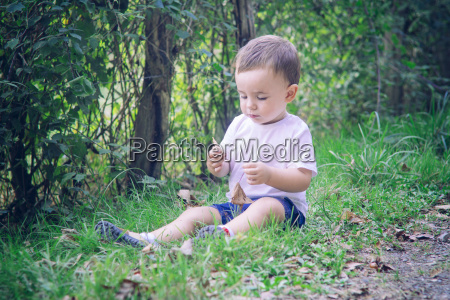baby boy sitting on the grass