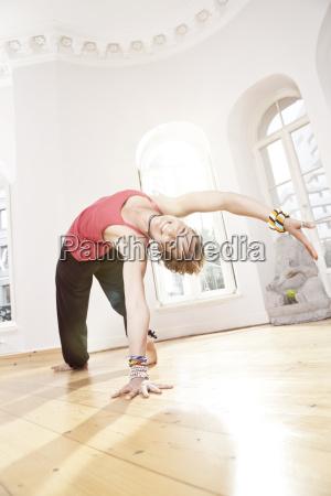 frau haelt setu bandha sirasasana yoga