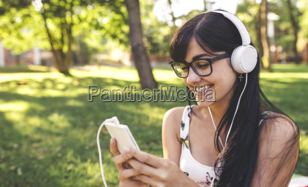 happy young woman in park listening
