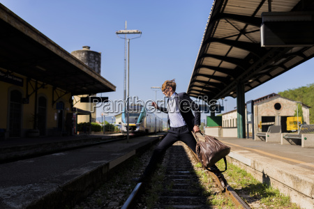 young businessman jumping over tracks