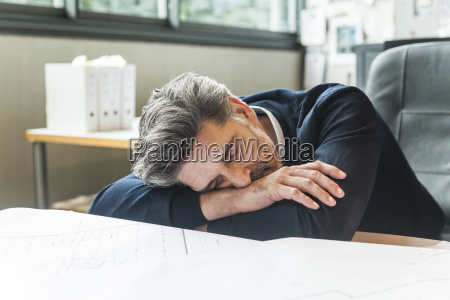 overworked architect sleeping at desk