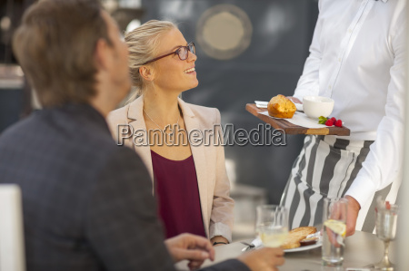 waiter serving food at table for