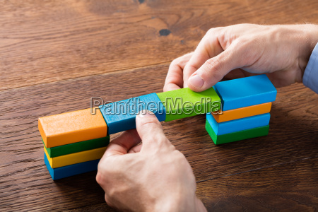 person hand building blocks