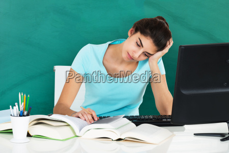 woman studying on desk in classroom