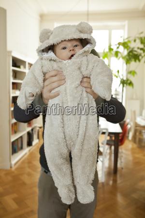 baby in bear costume being held