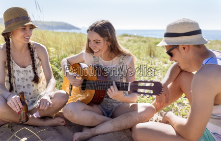 smiling teenage girl playing guitar for