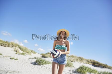 junge frau am strand spielt beachvolleyball