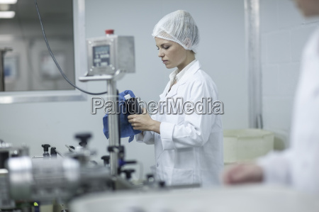 woman in pharmaceutical plant cleaning flask