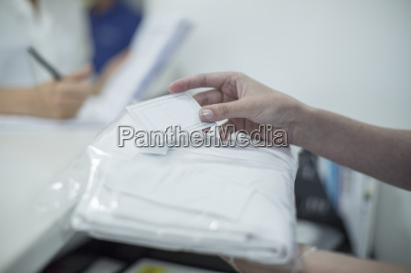 woman holding white coat in plastic