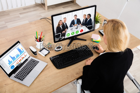 businesswoman videoconferencing on desktop computer