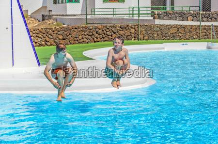 zwei freunde springen in den pool
