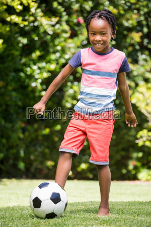 smiling boy kicking the ball