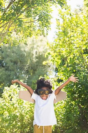 junge spielt als flieger im park