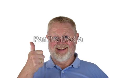 lachender senior haelt daumen hoch