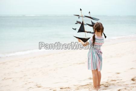 maedchen spielen am strand fliegen drachen