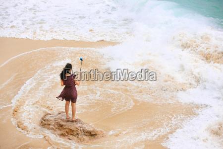 weiblich nehmen selfie am strand rueckansicht