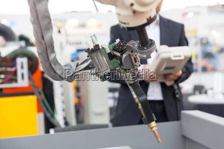 industrielle schweiss roboterarm verschwommenes operator im