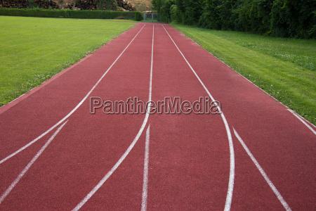 sportplatz mit roter laufstrecke und weissen