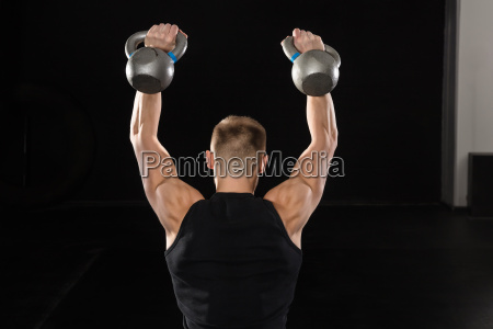 man doing exercise with kettle bell
