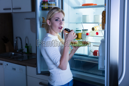 woman eating donut secretly from fridge