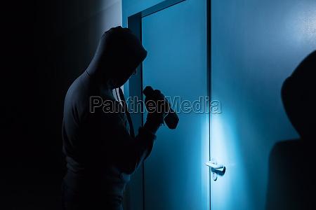 einbrecher holding taschenlampe vor der tuer