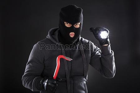 portraet eines einbrechers auf schwarzem hintergrund