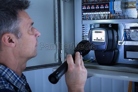 elektriker der einen fusebox prueft