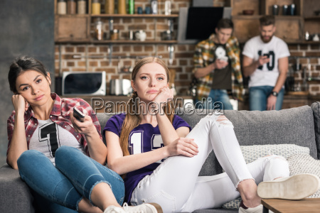 young upset women sitting on sofa