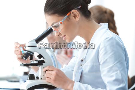 seitenansicht der jungen laechelnden frau wissenschaftler