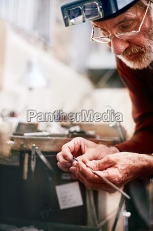 konzentriert maennlichen juwelier in der werkstatt