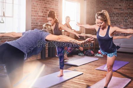 frauen die yoga praktizieren krieger 3