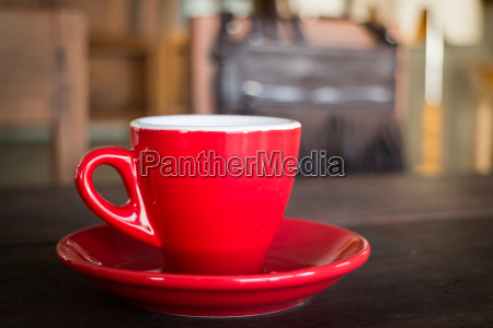 red cup of coffee on wooden