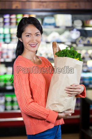 woman holding groceries in paper bag