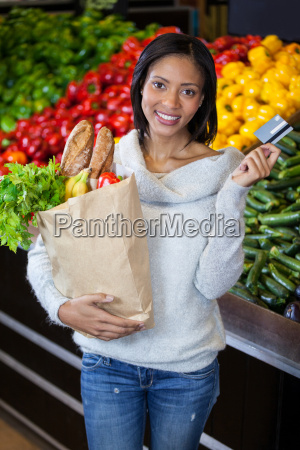 woman holding credit card and grocery