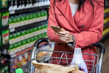 frau die handy beim einkaufen verwendet