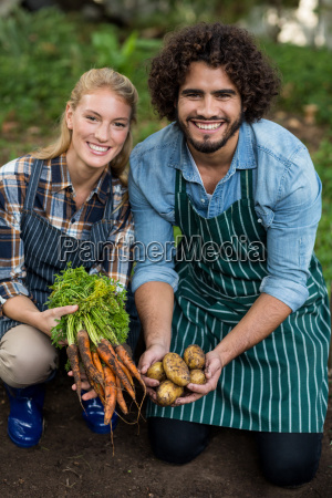 gardeners holding harvested carrots and potatoes