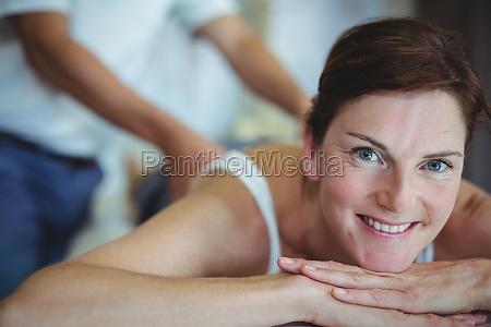 frau erhaelt rueckenmassage von physiotherapeut