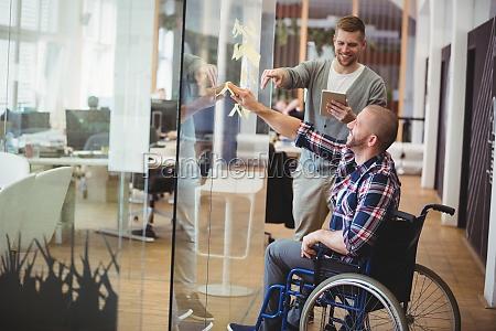 geschaeftsmann unterstuetzt handicap kollegen in kreativem