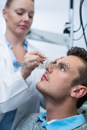female optometrist putting eye drop in
