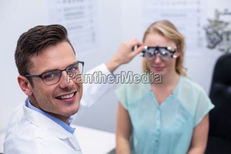 optometrist examining female patient with phoropter