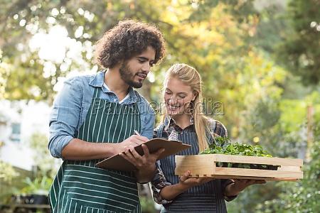 man writing on clipboard while gardener