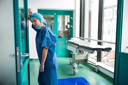 sad chirurg lehnt gegen die glastuer