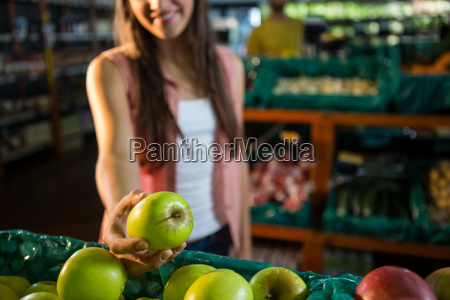 woman selecting a green apple in