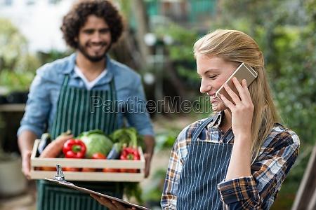 female gardener talking on cellphone while